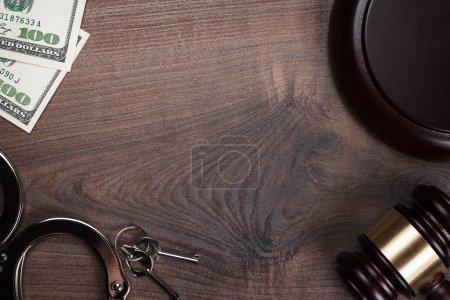 Photo pour Marteau de menottes et de l'argent sur le fond en bois - image libre de droit