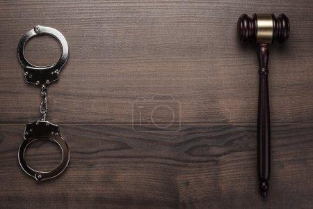 Photo pour Menottes et marteau de juge sur fond de bois brun - image libre de droit