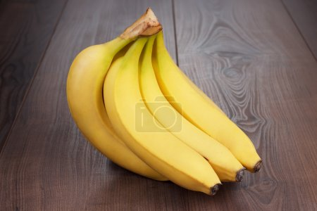 Foto de Plátanos frescos en el fondo de madera marrón - Imagen libre de derechos
