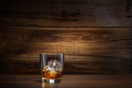 Photo for Glass of whiskey with ice on a wooden background - Royalty Free Image