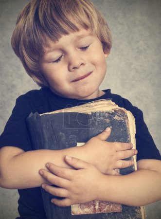 Photo for Little boy hugging an old book, he is happy - Royalty Free Image