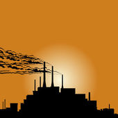 Circuit of industrial buildings and smoking chimneys against the setting sun