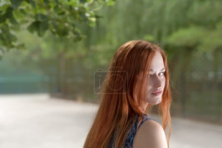 Red haired woman looking back