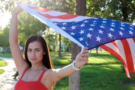 Photo for Serious young woman holding american flag flying by the wind - Royalty Free Image