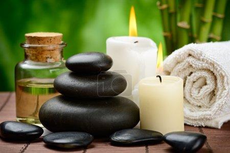 Photo pour Pierres de basalte zen et huile de massage sur le tapis en bois - image libre de droit