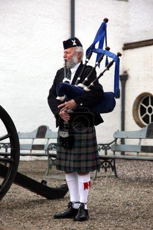 EDINBURGH, SCOTLAND, UNITED KINGDOM - JUNE 16 : Unidentified Scottish Bagpiper playing music with bagpipe at Edinburgh