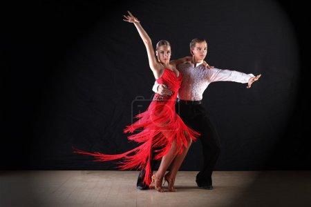 Photo pour : Danseurs latino dans la salle de bal sur fond noir - image libre de droit