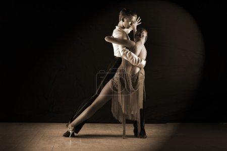 Photo pour Danseurs latino dans la salle de bal contre sur fond noir - image libre de droit