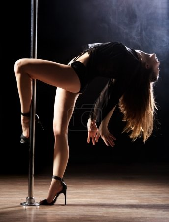 Photo for Young sexy pole dance woman, dark background - Royalty Free Image