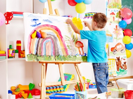 Photo for Child painting at easel in school. Education. - Royalty Free Image