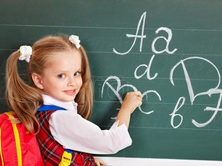 Photo pour Écolier écrivant sur le tableau noir dans la salle d'école . - image libre de droit