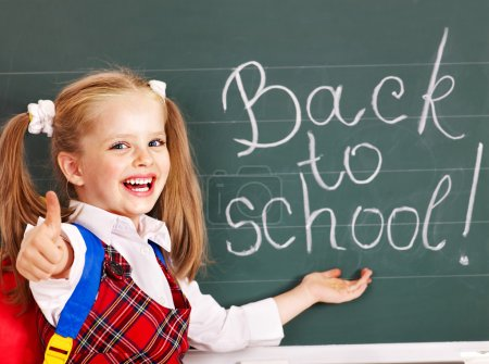 Photo for Happy child with backpack writting on blackboard. - Royalty Free Image