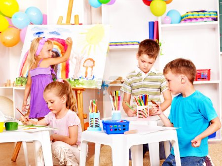 Photo for Group child painting at easel in school. - Royalty Free Image