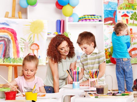 Photo for Children with teacher painting at easel in school. - Royalty Free Image