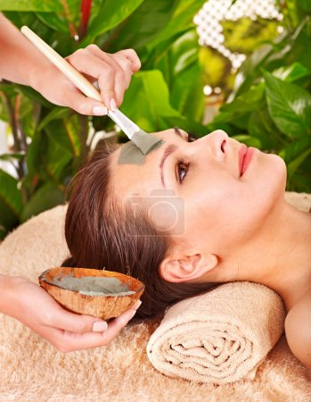 Photo for Woman with clay facial mask in beauty spa. - Royalty Free Image