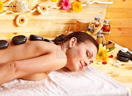 Photo pour Femme se pierres chaudes massage dans le spa en bois. - image libre de droit