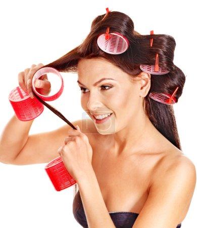 Woman wear hair curlers on head.