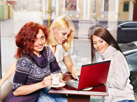 Photo for Three young women at laptop drinking coffee in a cafe. - Royalty Free Image
