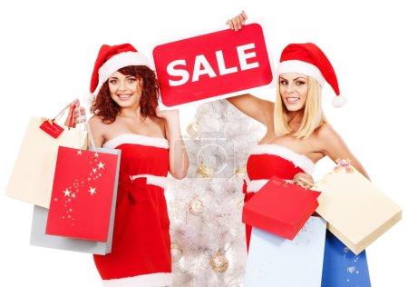 Photo pour Femmes dans Santa chapeau tenant signe disant vente et boîte cadeau . - image libre de droit