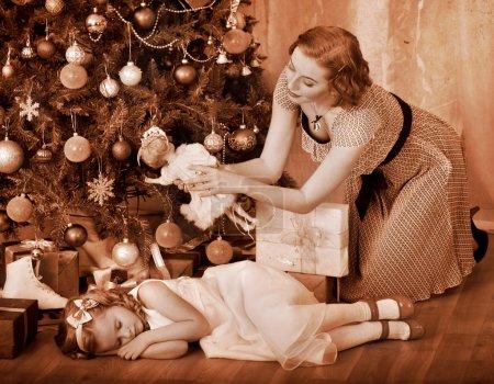 Photo pour Enfant avec la mère reçoit près de sapin de Noël. noir et blanc rétro. - image libre de droit