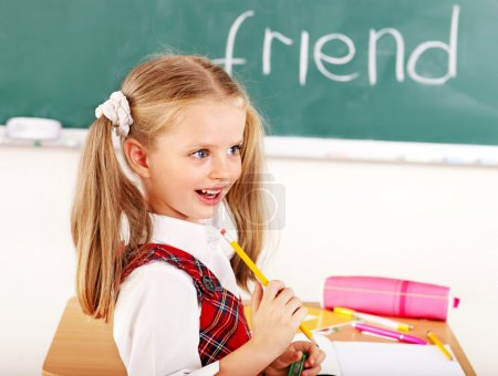 Photo for Schoolchild in classroom with blackboard. - Royalty Free Image