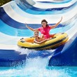 Child with mother on water slide at aquapark. Summ...