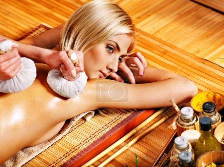 Photo pour Femme blonde se faire masser la balle à base de plantes dans le spa . - image libre de droit