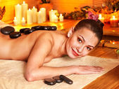 Woman getting stone therapy massage in bamboo spa