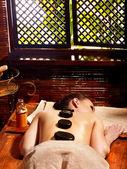 Woman having Ayurvedic stone massage.