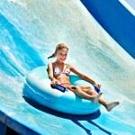 Child on water slide at aquapark. Summer holiday....
