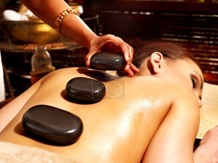 Woman having Ayurvedic stone massage.