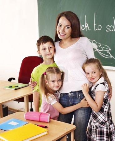 Children in classroom near blackboard.