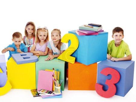 Children sitting at cube.