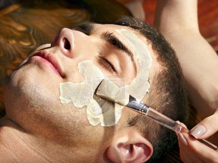 Photo pour Homme avec masque facial argile dans spa beauté. - image libre de droit