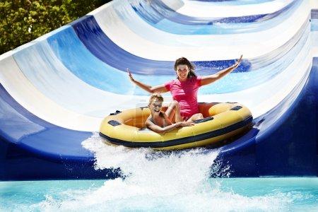Photo pour Enfant avec sa mère sur toboggan aquatique à Aquapark. Vacances d'été . - image libre de droit