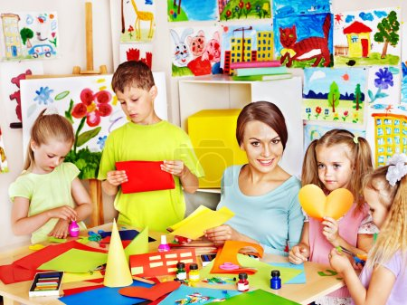 Photo for Children cutting out scissors paper in preschool. - Royalty Free Image