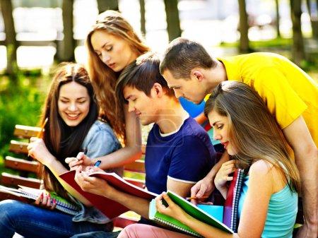 Photo pour Étudiant de groupe avec ordinateur portable sur banc extérieur . - image libre de droit