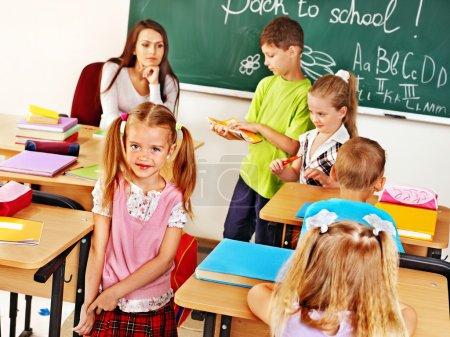 Photo pour Enfants avec professeur dans la salle de classe près du tableau noir  . - image libre de droit