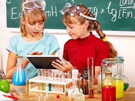 Photo pour Enfant tenant le comprimé pc en classe de chimie . - image libre de droit