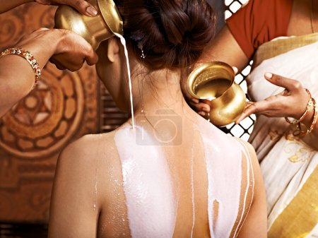 Woman having Ayurvedic milk spa treatment.