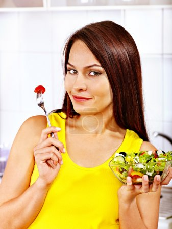 Photo for Happy woman eating salad at kitchen. - Royalty Free Image