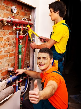 Photo for Happy men worker fixing heating system with a special tool - Royalty Free Image
