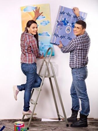 Photo pour Happy famille colle papier peint à la maison . - image libre de droit