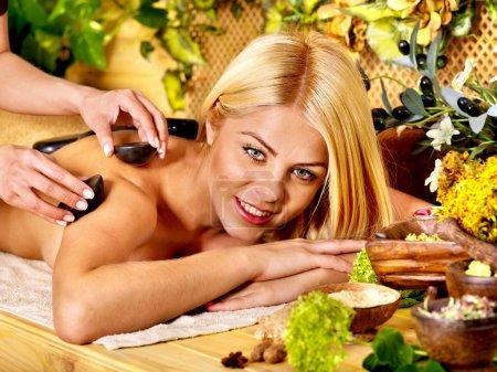 Woman getting stone massage .