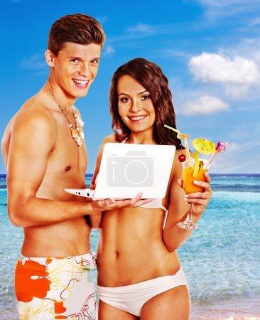 Photo for Couple with laptop at beach. Summer outdoor. - Royalty Free Image