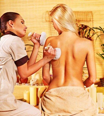 Woman getting herbal ball massage  .