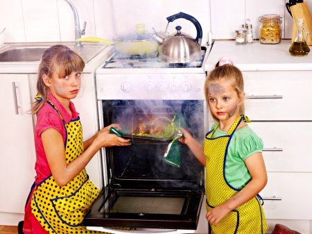 Children with  burned chicken cooking at kitchen....