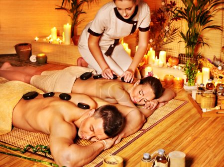 Woman and man getting stone therapy massage