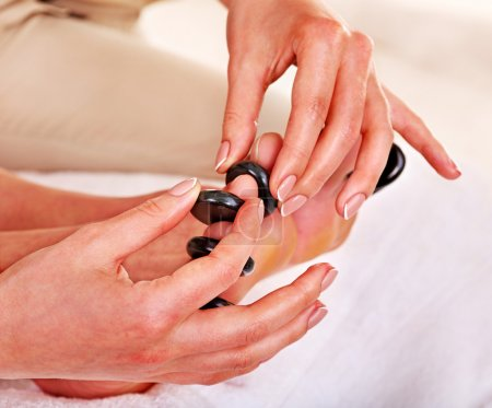 Woman receiving stone massage on feet.