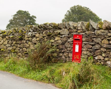 Old King George red post box in stone wall
